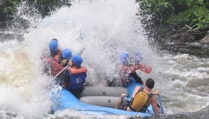 Wave breaking over a blue rubber raft full of paddlers in a tier
