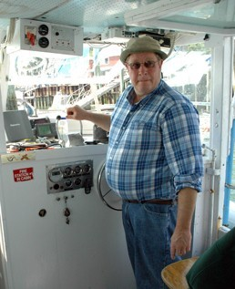 Tour boat captain in blue shirt standing at the helm of his boat
