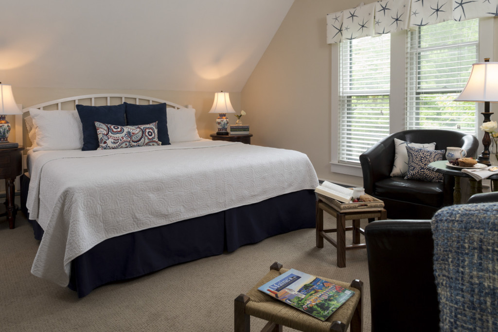 king bed room with bed w/ white duvet, 2 chairs and stools in seating area