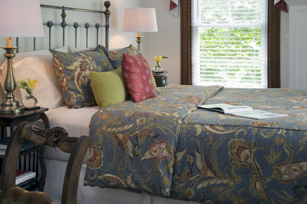 Close-up of bed, matching paisley gray pillows, sides tables and window in background
