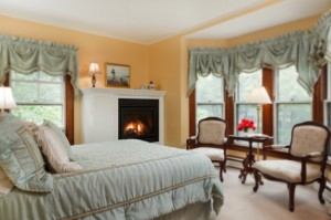 Room w/ yellow walls, blue hassled bedspread, fireplace and bay window seating area