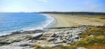 Long white sand beach sandwiched between a rocky headland and low bush