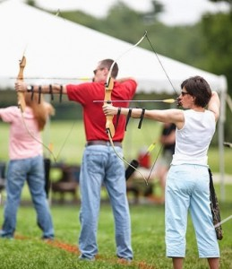 Line of people with bows drawn in an archery class