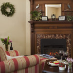 carved mahogany mantelpiece behind esy chair, wine glasses on a table and a fire burning in the fireplace