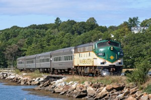 green & silver diesel engine approaching w/ 4 passengers over small bridge