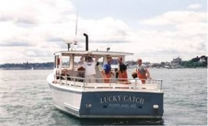 White & Blue hulled lobster boat with smiling crew aboard