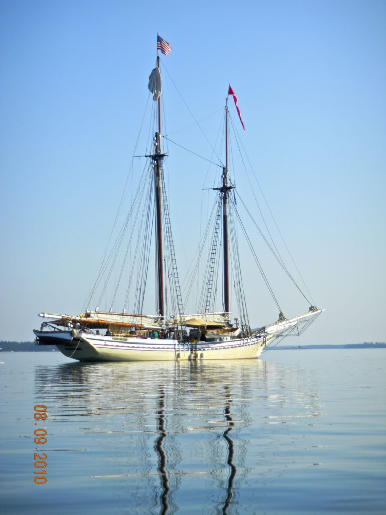 Yellow & white hulled large schooner at anchor with blue sky behind boating