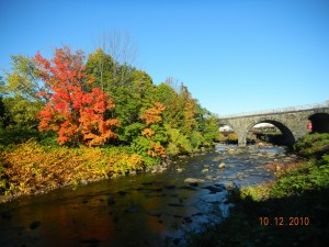 sunlit fall photo of red blazing maple above a rocky river with stone bridge in the backgroundDSCN0379