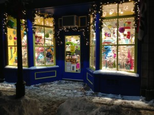 Shop window & snowy night sidewalk in front of pretty Christmas dressed shop window