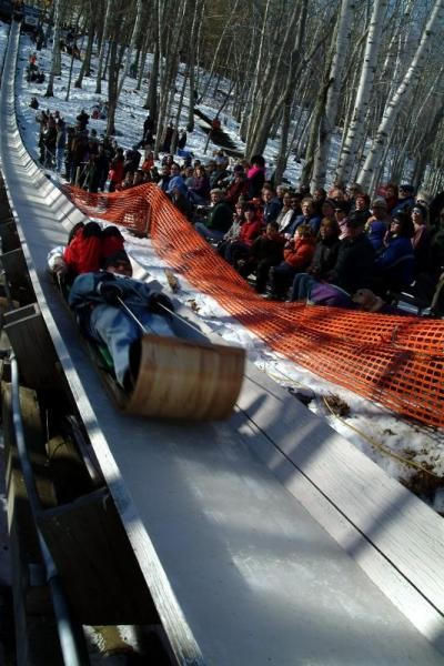 toboggan team heading downhill in an iced chute with crowd in background