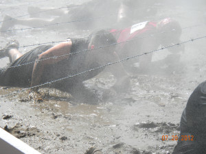 runners in athletic clothes, crawling under barbed wire through mud and mist