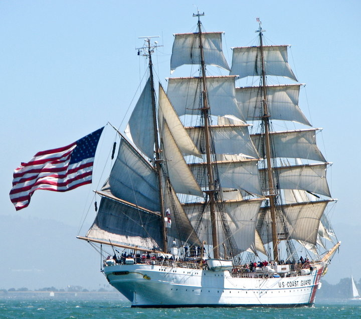 300' white square rigger under full sail with large American flag flying from aft sail.