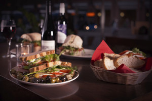 Italian sandwiches on tabletop with wine in background