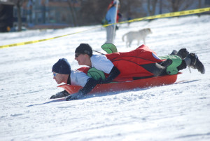 2 people racing downhill on a red plastic sled