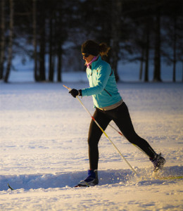 Cross country skier crossing meadow at twilight