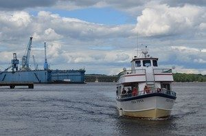 excursion boat heading upriver with shipyard in the background