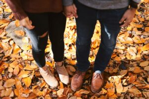 Couple's feet in fall leaves